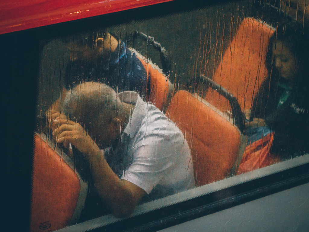 A rainy day on a bus with a man with his head in his hands.
